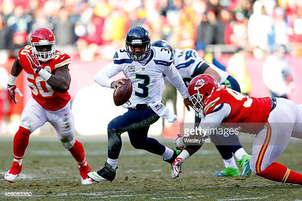 Russell Wilson of the Seattle Seahawks scrambles under pressure from Justin Houston and Kevin Vickerson of the Kansas City Chiefs during the game at...