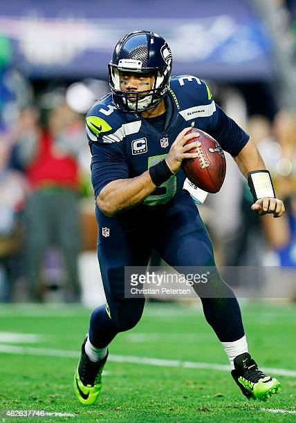 Russell Wilson of the Seattle Seahawks scrambles with the ball against the New England Patriots in the first quarter during Super Bowl XLIX at...