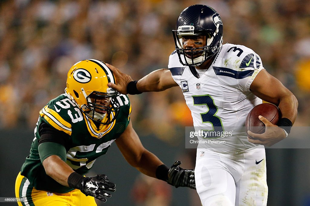 Russell Wilson #3 of the Seattle Seahawks stiff arms Nick Perry #53 of the Green Bay Packers during the third quarter in their game at Lambeau Field on September 20, 2015 in Green Bay, Wisconsin.