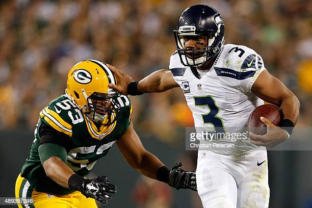Russell Wilson of the Seattle Seahawks stiff arms Nick Perry of the Green Bay Packers during the third quarter in their game at Lambeau Field on...