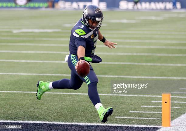 Russell Wilson of the Seattle Seahawks stretches the ball into the end zone for a touchdown against the Los Angeles Rams during the third quarter at...