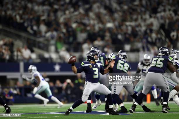 Russell Wilson of the Seattle Seahawks throws against the Dallas Cowboys in the second quarter of the Wild Card Round at ATT Stadium on January 05...