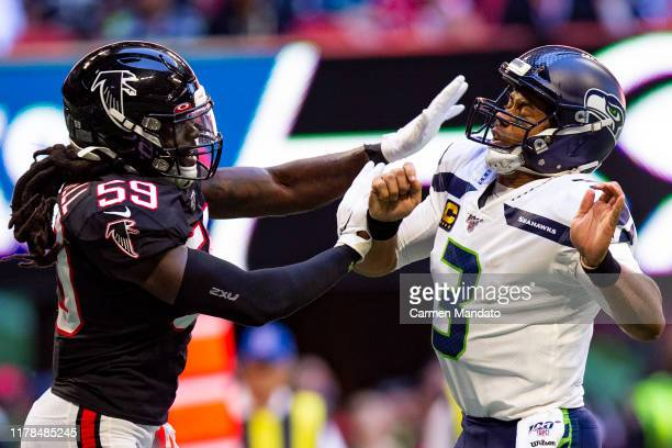Russell Wilson of the Seattle Seahawks under pressure from De'Vondre Campbell of the Atlanta Falcons during the first half of a game at MercedesBenz...