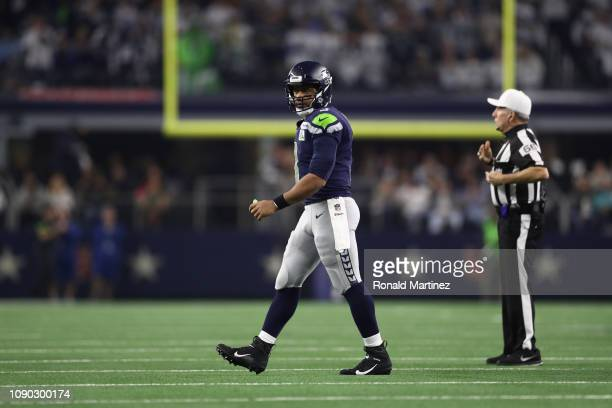 Russell Wilson of the Seattle Seahawks walks off the field after falling short on third down against the Dallas Cowboys in the Wild Card Round at ATT...