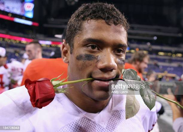 Russell Wilson of the Wisconsin Badgers celebrates with a rose after they won 42-39 against the Michigan State Spartans during the Big 10 Conference...