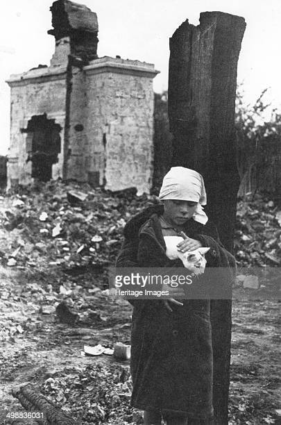 Russia after the Germans had gone World War II c1944 A girl and her pet cat wander through the rubble