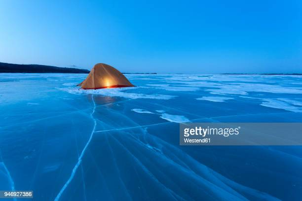 russia, amur oblast, illuminated tent on frozen zeya river at blue hour - temporary stock pictures, royalty-free photos & images