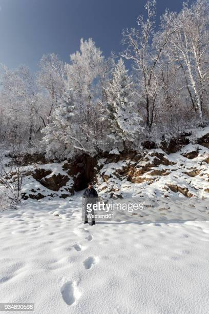 Russia, Amur Oblast, man in snow-covered nature
