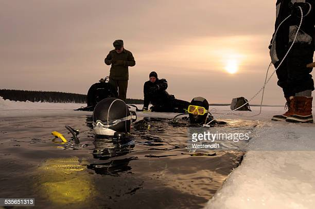 russia, arctic circle dive centre, polar circle, ice divers at hole - sea swimming stock photos and pictures