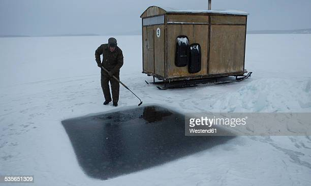 Russia, polar circle, White Sea, man preparing hole for ice diving