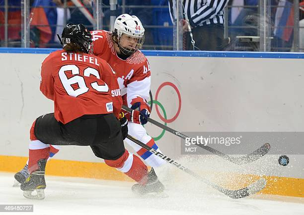 Russia defenseman Alexandra Kapustina slips the puck past Switzerland forward Anja Stiefel in the first period of a women's hockey quarterfinal game...