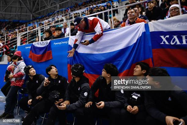 A Russia fan asks to take a photo of a caught puck in the men's gold medal ice hockey match between the Olympic Athletes from Russia and Germany...