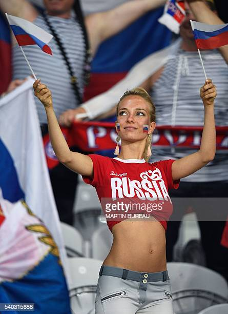 A Russia fan holds Russian flags as she waits for the start of the match before the Euro 2016 group B football match between Russia and Slovakia at...