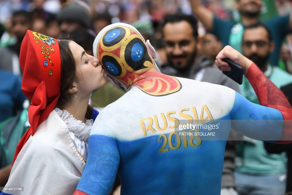 Russia fan kisses another supporter before the start of the Russia 2018 World Cup Group A football match between Russia and Saudi Arabia at the Luzhniki Stadium in Moscow on June 14, 2018. (Photo by Patrik STOLLARZ / AFP) / RESTRICTED