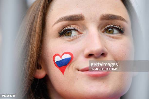 A Russia fan smiles before the start of the Russia 2018 World Cup Group A football match between Uruguay and Russia at the Samara Arena in Samara on...