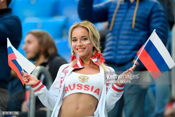 A Russia fan waves flags prior to the Russia 2018 World Cup Group A football match between Russia and Egypt at the Saint Petersburg Stadium in Saint...