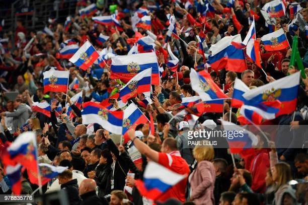 TOPSHOT Russia fans celebrate during the Russia 2018 World Cup Group A football match between Russia and Egypt at the Saint Petersburg Stadium in...