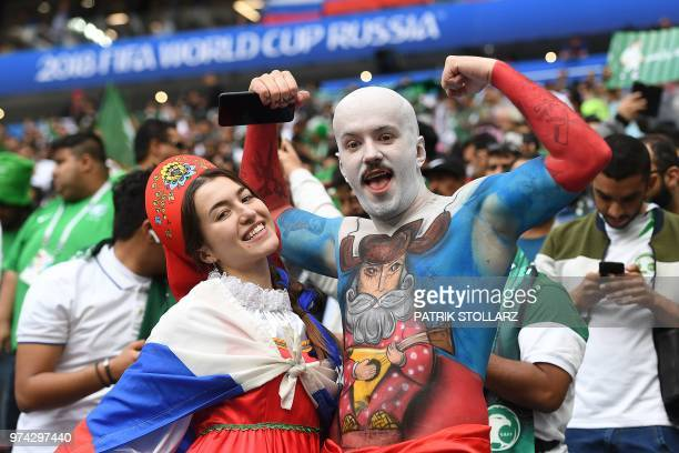 TOPSHOT Russia fans pose as they wait for the start of the Russia 2018 World Cup Group A football match between Russia and Saudi Arabia at the...