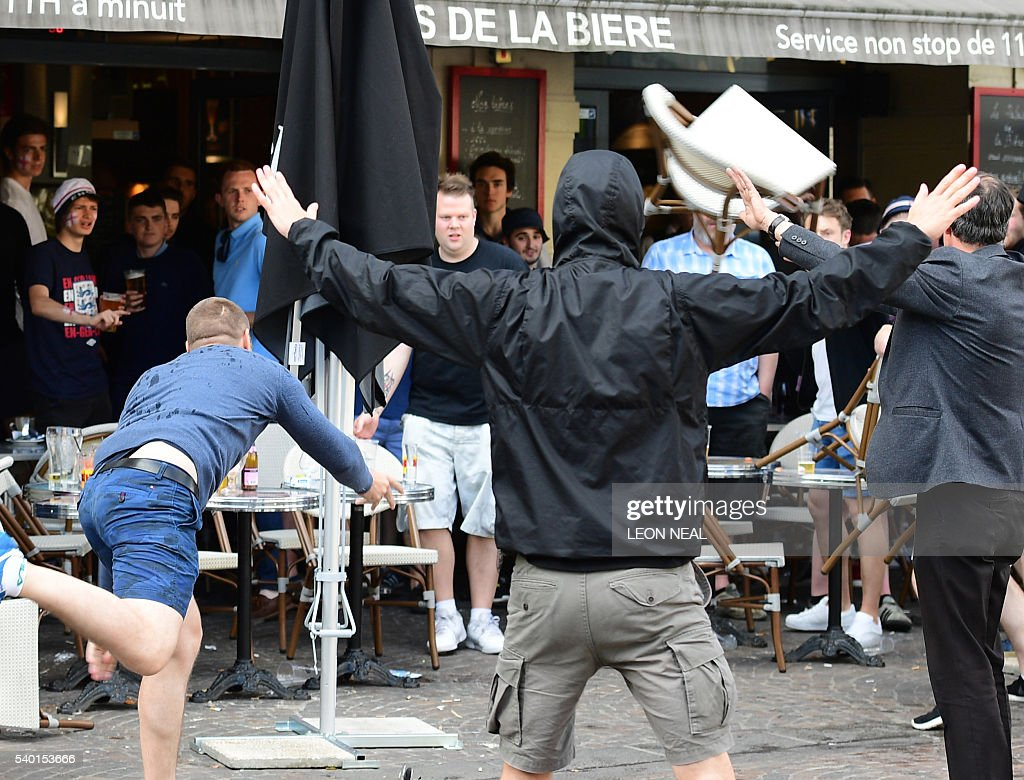 A Russia football supporter lobs a chair towards England fans sitting in a cafe in the northern city of Lille on June 14, 2016, three days after Russian and England supporters clashed in Marseille. A group of 43 Russian football supporters have been placed in custody in southern France and could appear in court over fan violence in Marseille, officials said June 14. NEAL