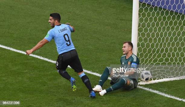 Russia goalkeeper Igor Akinfeev reacts as Luis Suarez of Uruguay celebrates their second goal scored by Diego Laxalt during the 2018 FIFA World Cup...