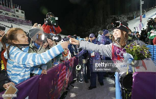 SOCHI Russia Japanese freestyle skier Ayana Onozuka hands a necklace back to her mother Yukari after winning the bronze medal in the women's ski...