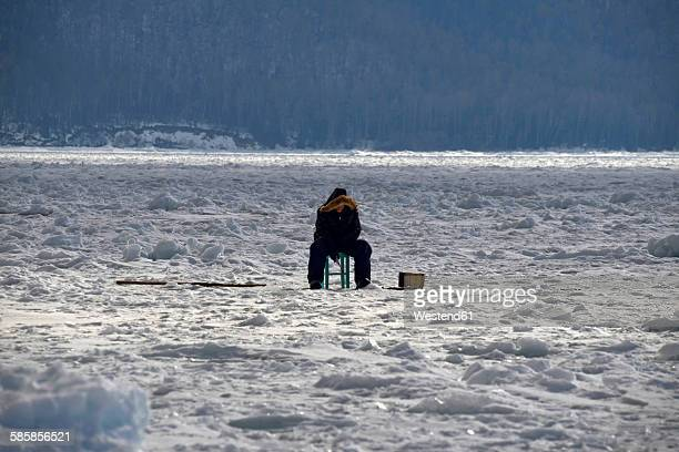 Russia, Lake Baikal, ice fishing on frozen lake