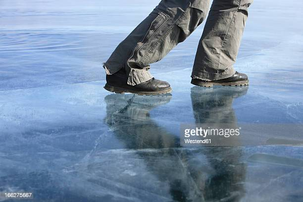 Russia, Lake Baikal, man walking on frozen lake, low section
