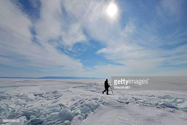 Russia, Lake Baikal, man walking on frozen lake