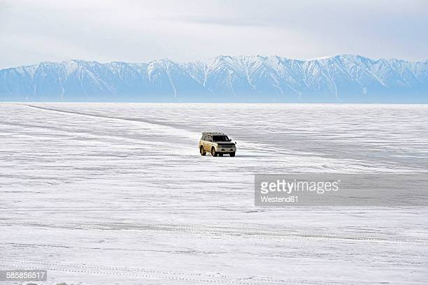 Russia, Lake Baikal, pickup truck driving on frozen lake