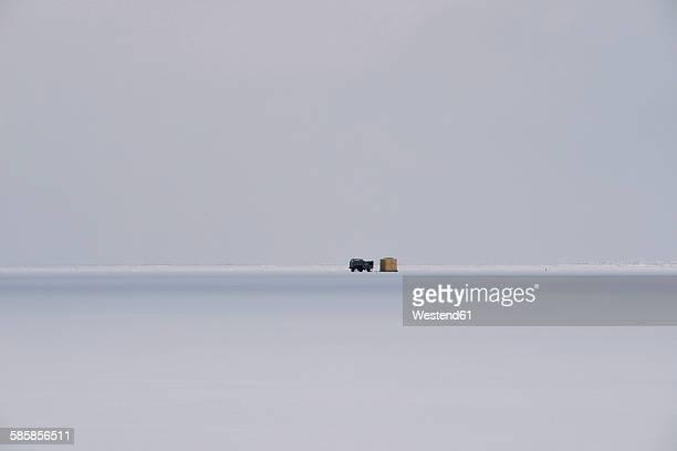 Russia, Lake Baikal, pickup truck on frozen lake beside hut for ice fishing