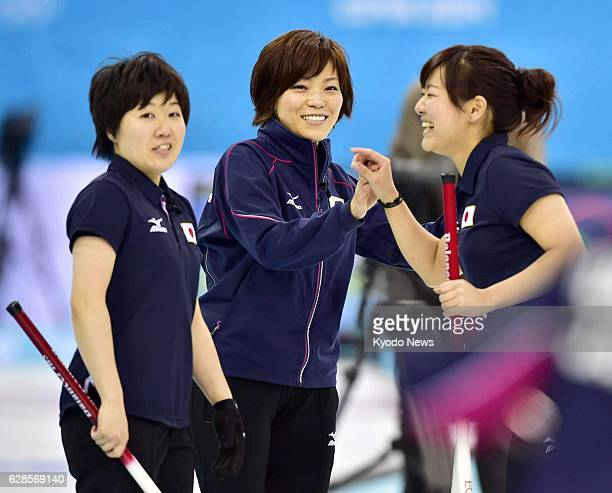 Russia - Members of the Japanese women's curling team - Michiko Tomabechi, Ayumi Ogasawara, Chinami Yoshida - celebrate after scoring points during...
