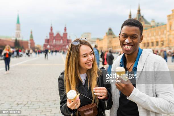Russia, Moscow, couple eating icecream in the city