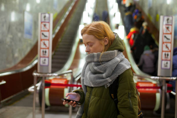 Russia, Novosibirsk, Young woman with smartphone standing by escalator