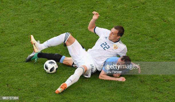 Russia player Artem Dzyuba is challenged by Diego Godin of Uruguay during the 2018 FIFA World Cup Russia group A match between Uruguay and Russia at...