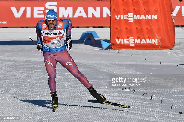 Russia' Sergey Ustiugov sprints to cross the finish line and win the Men's 10 km individual free competition of the Tour de Ski Cross Country World...