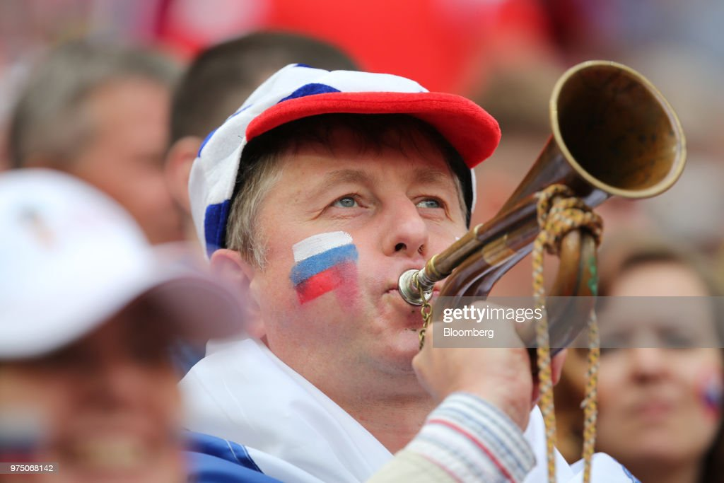 A Russia soccer fan blows a bugle during the opening ceremony of the FIFA World Cup in the Luzhniki stadium in Moscow, Russia, on Thursday, June 14, 2018. President Vladimir Putin has spent six years and more than $11 billion preparing nearly a dozen Russian cities to host the soccer World Cup, the biggest such event the countrys held since the collapse of the Soviet Union. Photographer: Andrey Rudakov/Bloomberg via Getty Images