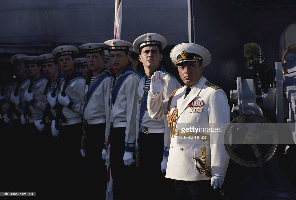Navy officers standing in row on deck of naval ship : News Photo