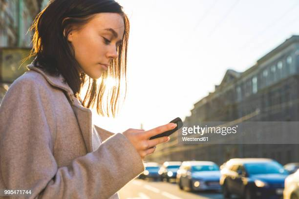 russia, st. petersburg, young woman using smartphone in the city - femme russe photos et images de collection