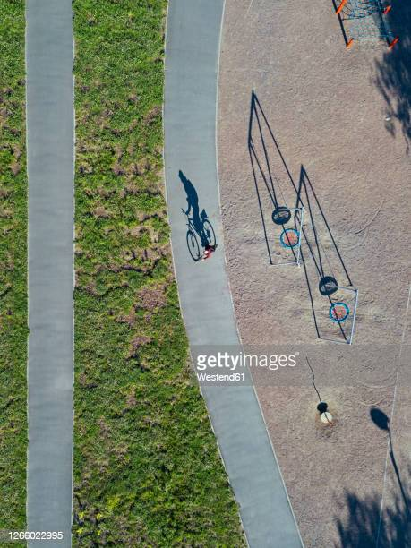russia, tikhvin, man riding bicycle on path near park playground, aerial view - vertical stock pictures, royalty-free photos & images