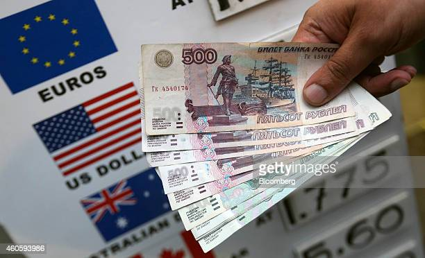 Russian 500 and 1000 denomination ruble banknotes are held for a photo outside the Thomas Exchange Global Ltd foreign currency exchange in London UK...