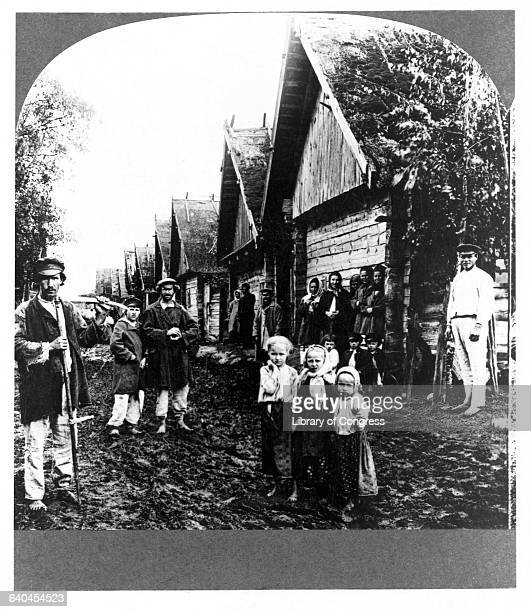 Russian adults and children, exiled in Siberia, stand on a dirt road next to wooden huts with pointed roofs.