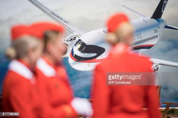 Russian airlines Aeroflot air hostesses stand in front of an advertizing board depicting the new Rusian Sukhoi Superjet 100 airliner on July 18 2017...