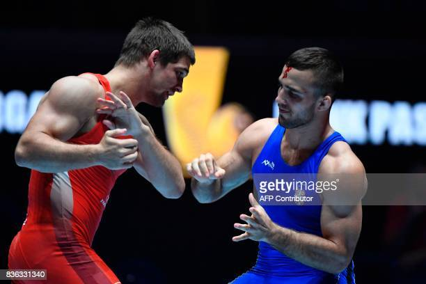 Russian Aleksandr Chekhirkin injured on the forehead and Serbian Victor Nemes fight during the men's GrecoRoman style 75 kg category final during the...
