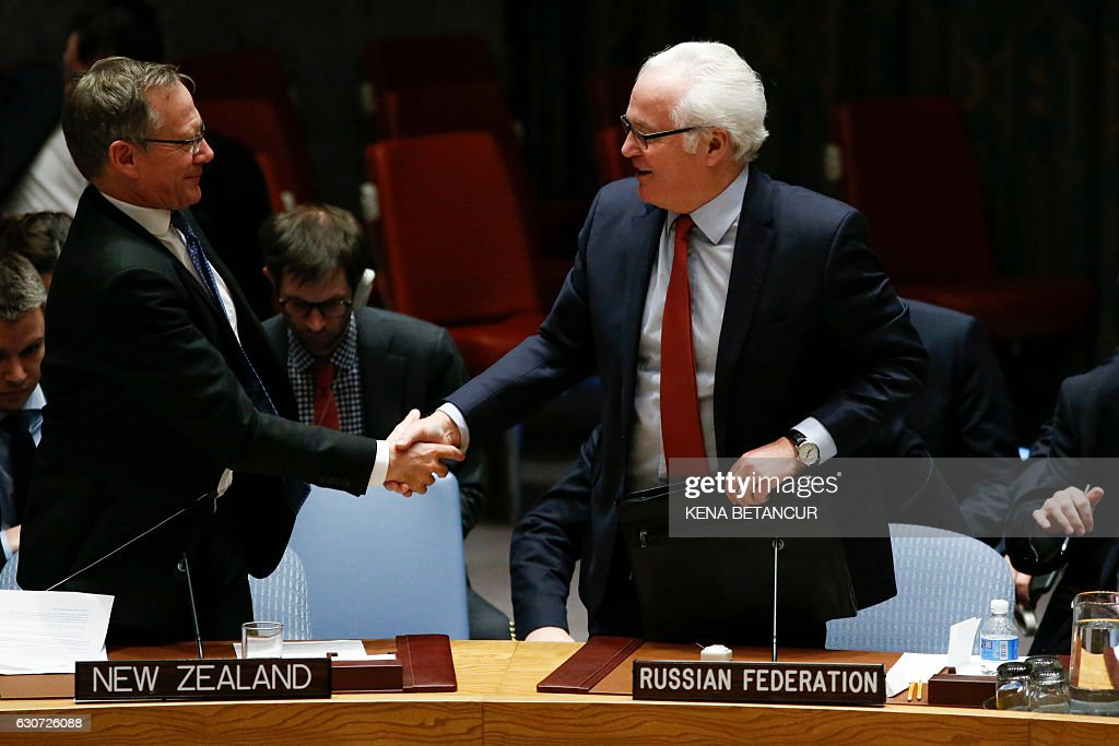 Russian Ambassador to the UN Vitaly Churkin (R) shake hands with Gerard van Bohemen, the permanent representative of New Zealand to the U.N at the UN Security Council which voted on Russian-Turkish peace plan for Syria, on December 31, 2016, at UN Headquarters in New York. The Security Council unanimously approved the resolution. / AFP / KENA
