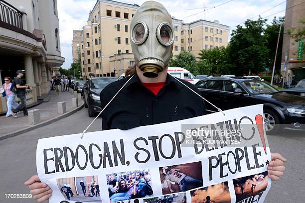 A Russian anarchist activist holds a cardboard during a protest against Turkey's Prime Minister Recep Tayyip Erdogan held near the Turkish embassy in...