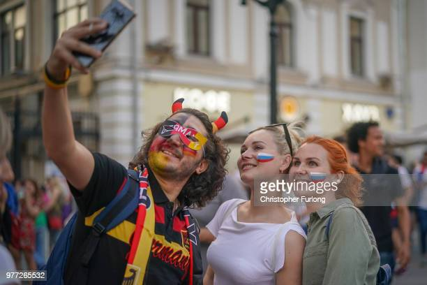 Russian and German World Cup football fans come together for a selfie as they enjoy the party atmosphere on Nikolskaya Street near Red Square on June...