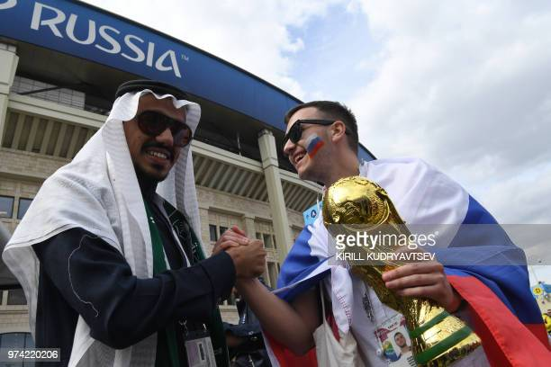 A Russian and Saudi supporter pose with a replica of the World Cup trophy ahead of the Russia 2018 World Cup Group A football match between Russia...
