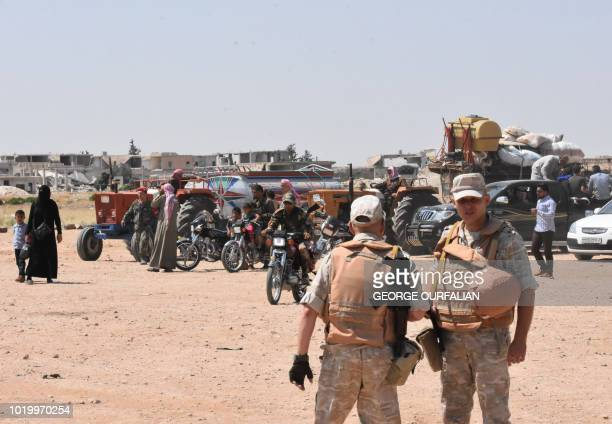 Russian and Syrian forces stand guard as civilians enter the Abu Duhur crossing on the eastern edge of Idlib province on August 20 2018 Civilians are...