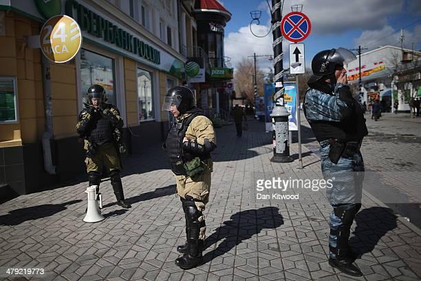 Russian and Ukrainian Berkut riot police stand in central Simferopol on March 17 2014 in Simferopol Ukraine Voters on the autonomous Ukrainian...