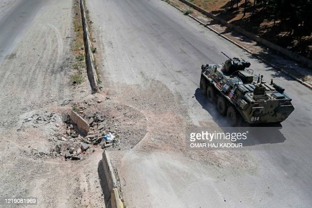 Russian armoured vehicle drives as part of a joint Turkish-Russian military patrol along the M4 highway, which links the northern Syrian provinces of...
